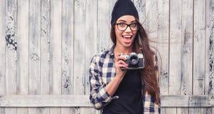 Muchacha sonriente en vidrios con la cámara del vintage Fotos de archivo