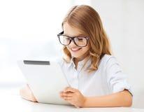 Muchacha sonriente en vidrios con PC de la tableta en la escuela Imagen de archivo libre de regalías