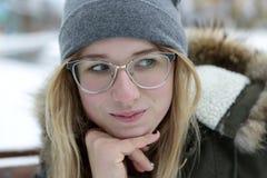 Muchacha sonriente en vidrios en invierno Imagenes de archivo