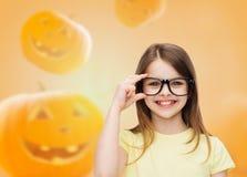 Muchacha sonriente en vidrios sobre fondo de las calabazas Imagenes de archivo