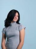 Muchacha sonriente encantadora en alineada gris Foto de archivo