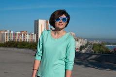 Muchacha sonriente encantadora en gafas de sol divertidas con el pelo del vuelo Fotografía de archivo libre de regalías