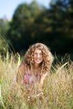 Muchacha sonriente entre la hierba alta Foto de archivo libre de regalías