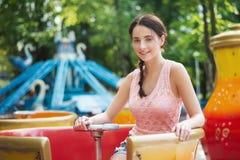 Muchacha sonriente feliz atractiva en un parque de atracciones que se sienta en el carrusel Imagen de archivo