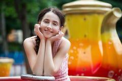 Muchacha sonriente feliz atractiva en un parque de atracciones que se sienta en el carrusel Imagenes de archivo