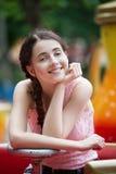 Muchacha sonriente feliz atractiva en un parque de atracciones que se sienta en el carrusel Foto de archivo