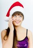 Muchacha sonriente feliz con el sombrero de Santa con un teléfono Foto de archivo libre de regalías