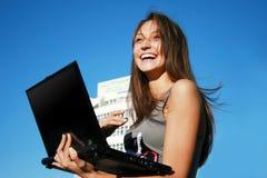 Muchacha sonriente feliz con la computadora portátil Imagenes de archivo