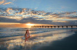 Muchacha sonriente feliz con las conchas marinas en la playa hermosa en la salida del sol Foto de archivo