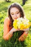 Muchacha sonriente feliz con las flores amarillas Imagen de archivo libre de regalías