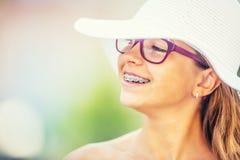 Muchacha sonriente feliz con los apoyos y los vidrios dentales Apoyos y vidrios de los dientes de la muchacha que llevan rubia ca Imagenes de archivo