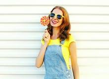 Muchacha sonriente feliz con una piruleta en el palillo Imágenes de archivo libres de regalías