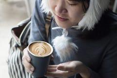 Muchacha sonriente feliz de los asiáticos hermosos jovenes que sostiene una taza de café caliente y que la huele, ropa del invier fotos de archivo libres de regalías