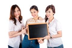 Muchacha sonriente feliz de tres asiáticos que sostiene la pizarra en blanco, primer imagen de archivo libre de regalías