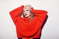 Muchacha sonriente feliz del inconformista en suéter hecho punto y el sombrero rojos que se divierten Muchacha linda en glusses c Imagen de archivo libre de regalías