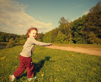 Muchacha sonriente feliz del niño que corre en hierba verde Fotografía de archivo libre de regalías