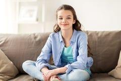 Muchacha sonriente feliz del preadolescente que se sienta en el sofá en casa Imagenes de archivo