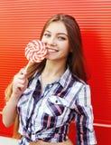 Muchacha sonriente feliz del retrato con la piruleta dulce del caramelo que se divierte sobre rojo Imagenes de archivo