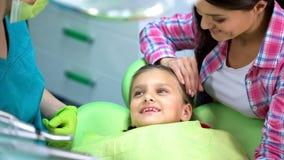 Muchacha sonriente feliz después del procedimiento de la odontología, dentista pediátrico bien capacitado fotografía de archivo