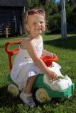 Muchacha sonriente feliz en coche del juguete Imagen de archivo
