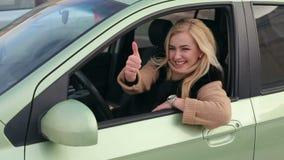 Muchacha sonriente feliz en el coche que muestra el pulgar para arriba almacen de metraje de vídeo