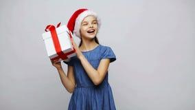 Muchacha sonriente feliz en el sombrero de santa que sacude la caja de regalo almacen de video