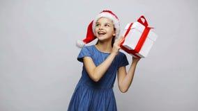 Muchacha sonriente feliz en el sombrero de santa que sacude la caja de regalo almacen de metraje de vídeo