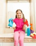 Muchacha sonriente feliz en los guantes de goma que presentan con el trapo en el cuarto de baño Foto de archivo libre de regalías