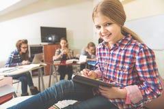 Muchacha sonriente feliz en sala de clase Imagen de archivo