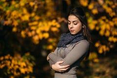 Muchacha sonriente feliz hermosa que lleva el vestido largo y la bufanda del otoño que se colocan en el bosque rodeado por los ár fotos de archivo