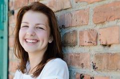Muchacha sonriente feliz joven que se coloca en el fondo de la pared de ladrillo Foto de archivo libre de regalías