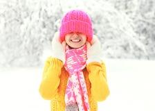 Muchacha sonriente feliz que lleva la ropa hecha punto colorida que se divierte en día de invierno Foto de archivo libre de regalías
