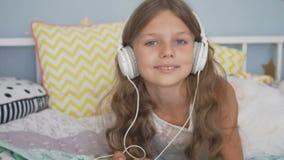 Muchacha sonriente feliz que miente con smartphone y los auriculares en la cama que escucha la música en casa metrajes
