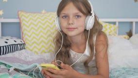 Muchacha sonriente feliz que miente con smartphone y los auriculares en la cama que escucha la música en casa almacen de video