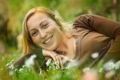 Muchacha sonriente feliz que miente en hierba en un prado Foto de archivo libre de regalías