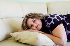 Muchacha sonriente feliz que miente en la almohadilla fotografía de archivo