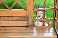 Muchacha sonriente feliz que mira hacia fuera entre las partes de madera de la casa del jardín Imagen de archivo libre de regalías