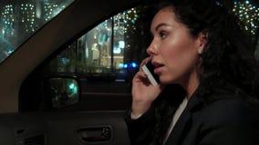 Muchacha sonriente feliz que monta en un taxi en la noche, sentándose en el asiento delantero y hablando en el smartphone almacen de video