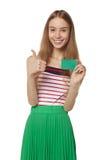 Muchacha sonriente feliz que muestra la tarjeta del crédito en blanco, en el backgroun blanco Fotos de archivo