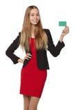 Muchacha sonriente feliz que muestra la tarjeta del crédito en blanco, en el backgroun blanco Imagen de archivo
