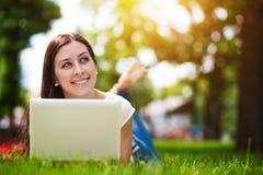 Muchacha sonriente feliz que pone en hierba con la computadora portátil Imágenes de archivo libres de regalías
