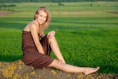 Muchacha sonriente feliz que se sienta al aire libre Fotografía de archivo libre de regalías