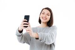 Muchacha sonriente feliz que toma el selfie en el teléfono móvil Fotos de archivo