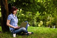 Muchacha sonriente feliz que trabaja en línea Imagen de archivo