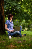 Muchacha sonriente feliz que trabaja en línea Fotografía de archivo libre de regalías