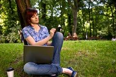 Muchacha sonriente feliz que trabaja en línea Fotos de archivo libres de regalías