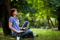 Muchacha sonriente feliz que trabaja en línea Imagenes de archivo