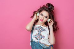 Muchacha sonriente fresca de la moda bonita escuchando la música en llevar de los auriculares ropa colorida con el pelo rizado so Fotografía de archivo