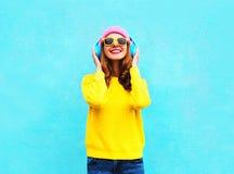 Muchacha sonriente fresca de la moda bonita que escucha la música en los auriculares que llevan un sombrero rosado colorido, gafa Fotografía de archivo libre de regalías