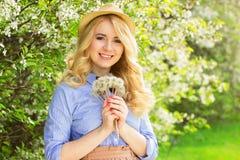 Muchacha sonriente hermosa con el pelo y las flores largos en el jardín fotos de archivo